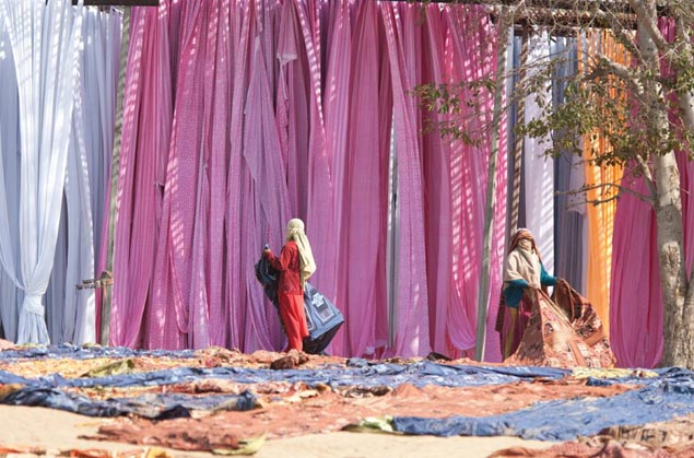 Women textile workers air rugs in Jaipur, Rajasthan. India Exposed by Clive Limpkin. The Subcontinent A-Z