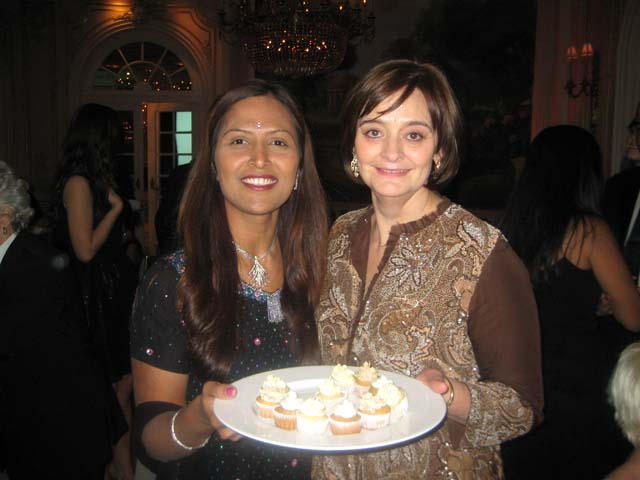 Parul Patel of The Cake Designer offers a tasting to former First Lady of the UK, Cherie Blair, at a fundraiser. Patel specializes in eggless vegetarian cakes.