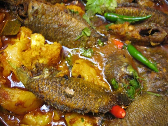 Bengali food centers around fish and this image shows Koi Fish with Cauliflower and Potato
