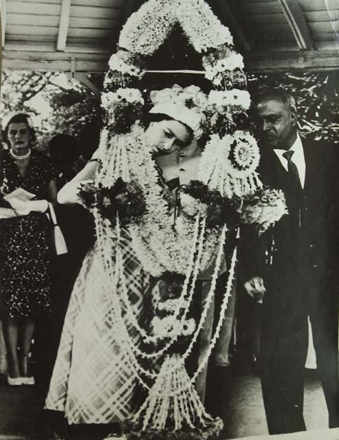 Homai Vyarawalla, Indian (1913 – 2012) Queen Elizabeth II examining a gigantic garland presented to her in Madras; 1961 Gelatin Silver Print Alkazi Collection of Photography