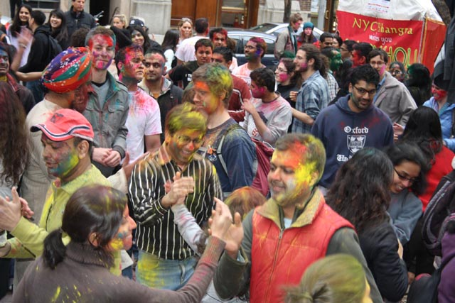 Revelers douse each other with colored powders for Holi