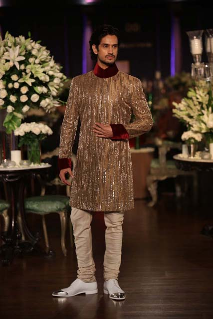 Gold sheGold sherwani with ruby red accents