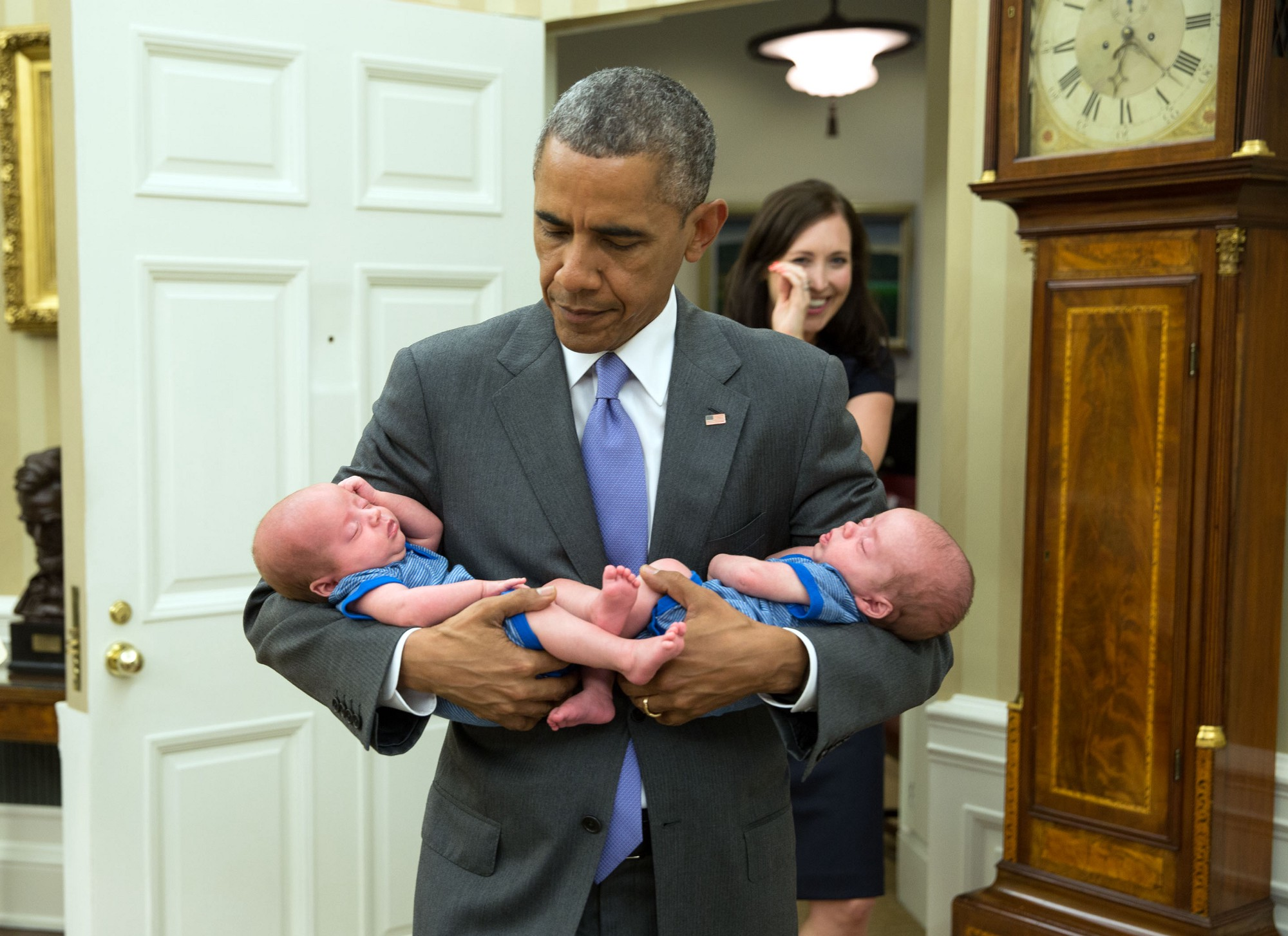 """The President carries the twin boys of Katie Beirne Fallon, Director of Legislative Affairs, into the Oval Office just a few months after they were born."" (Official White House Photo by Pete Souza)"