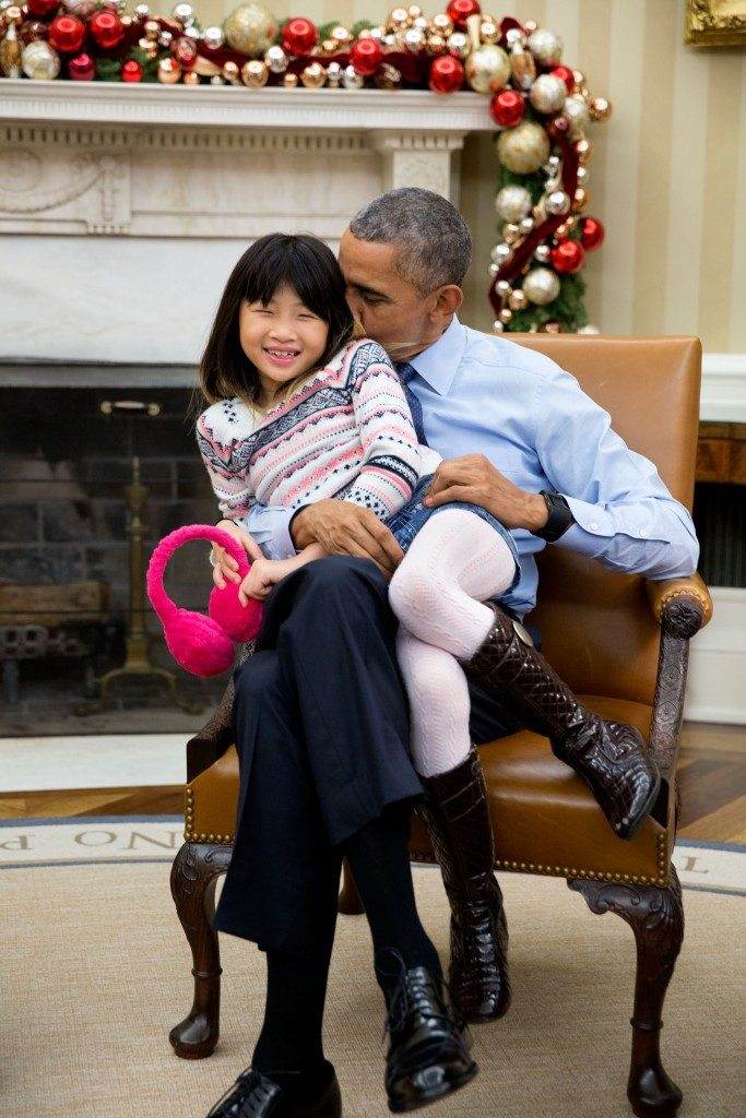 """The President snuggles with his niece Savita Ng after his sister, Maya Soetoro-Ng, and her family dropped by the Oval Office."" (Official White House Photo by Pete Souza)"