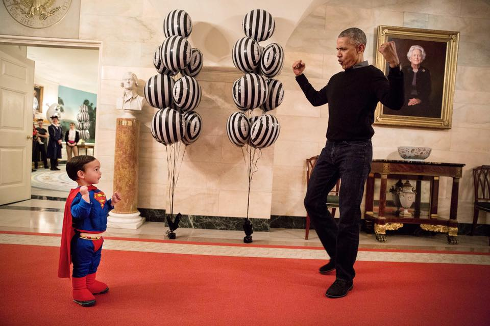 President Barack Obama flexes biceps with Superman Walker Earnest in the Lower Cross Hall of the White House, prior to welcoming local children to trick-or-treat for Halloween at the South Portico, Oct. 31, 2016. Walker is the son of Press Secretary Josh Earnest. (Official White House Photo by Pete Souza)