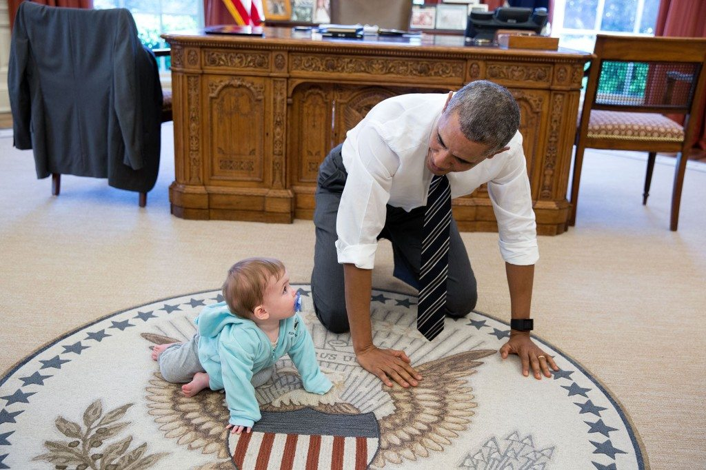 """6. April 14, 2016 """"The President is always asking staff to bring their babies and young kids by for a visit. Here, during a break between meetings one afternoon, the President crawled around in the Oval Office with Communications Director Jen Psaki's daughter Vivi."""" (Official White House Photo by Pete Souza)"""