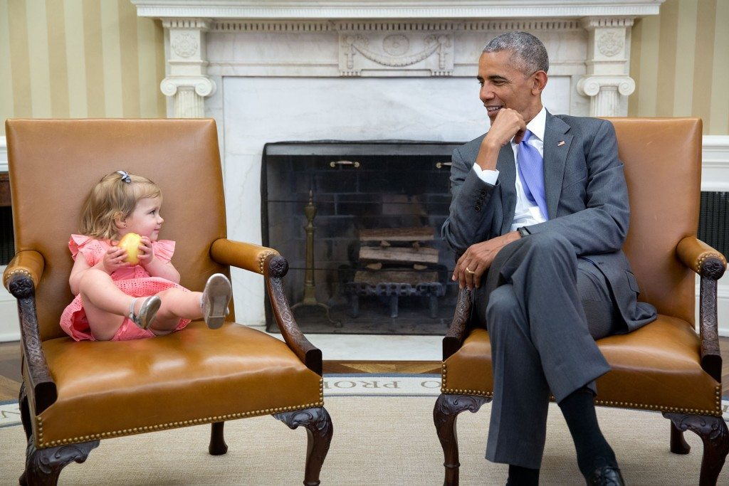 """7.June 22, 2016 """"The great thing about children is you just don't know what they will do in the presence of the President. So when David Axelrod stopped by the Oval Office with one of his sons' family, Axe's granddaughter, Maelin, crawled onto the Vice President's seat while the President continued his conversation with the adults. Then at one point, Maelin glanced over just as the President was looking back at her."""" (Official White House Photo by Pete Souza)"""
