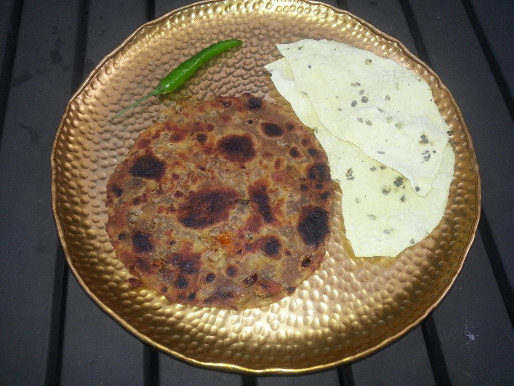 Sindhi Kokie and papad with a green chilie on the side