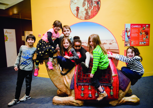 Children of all cultures ride on a camel