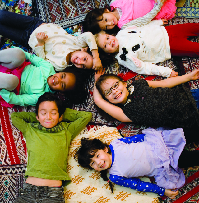 Children try out the rugs created by Muslim artisans